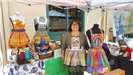 Woman standing next to the colorful aprons she created at Earth Day 2018