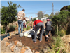 volunteers decorating garden with large rocks at Earth Day 2018